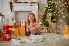 Upphetsad nyfiken liten flicka som ler, öppnande julgåvor Beautifully dekorerat julträd och hus med ljus och arkivbilder