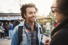Upphetsad och fascinerad ung afrikansk amerikanman som talar med vännen, medan vara in parkera som bär trendig kläder arkivfoto