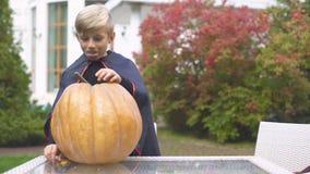 Upphetsad pojke i vampyrdräkt som snider pumpastålar-nolla-lyktan för allhelgonaafton arkivfilmer