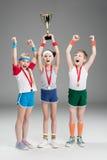 Upphetsad pojke och flickor med medaljer och mästarebägaren Arkivbilder