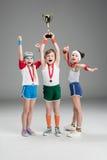 Upphetsad pojke och flickor med medaljer och mästarebägaren Arkivfoto