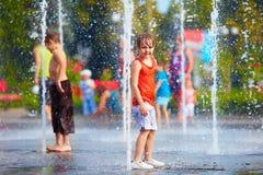 Upphetsad pojke som har gyckel mellan vattenstrålar, i springbrunn mig sommar Royaltyfria Foton