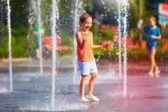 Upphetsad pojke som har gyckel mellan vattenstrålar, i springbrunn Sommar i staden Fotografering för Bildbyråer