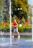 Upphetsad pojke som har gyckel mellan vattenstrålar, i springbrunn Sommar i staden Royaltyfria Bilder
