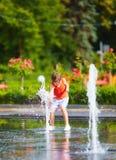 Upphetsad pojke som har gyckel mellan vattenstrålar, i springbrunn Sommar i staden Arkivbilder