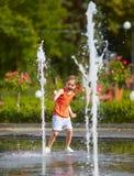 Upphetsad pojke som har gyckel mellan vattenstrålar, i springbrunn Sommar i staden Royaltyfri Foto