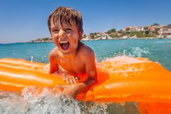 Upphetsad pojke som har gyckel som rider vågor i havet arkivbilder