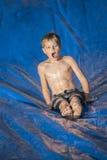 Upphetsad pojke som spelar på en snedsteg och snedsteg utomhus Arkivbild