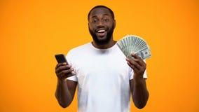 Upphetsad smartphone f?r Afro--amerikan maninnehav och dollar, online-pengar?verf?ring arkivfoto