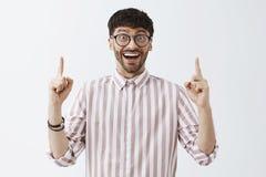 Upphetsad snygg lycklig man med skägget och kall frisyr för mörker i svarta exponeringsglas och randiga skjortan som lyfter index royaltyfri bild