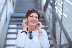 Upphetsad stilfull mogen kvinna i hörlurar som lyssnar till musik på gatan som bort ler royaltyfria foton