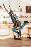 upphetsad stilig afrikansk amerikanarbetare som har gyckel och hoppar med kvasten royaltyfri bild