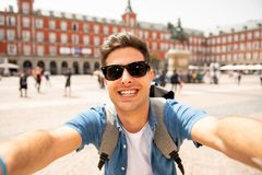 Upphetsad stilig ung caucasian turist- man som är lycklig och ta en selfie i Plazaborgmästaren, Madrid Spanien royaltyfri foto