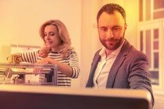 Upphetsad strävsam dam som fixar några problem, och hennes kollega som upp ser moment på rengöringsduken arkivfoton