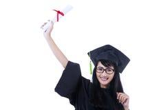 Upphetsad student i den isolerade avläggande av examenkappan - Fotografering för Bildbyråer