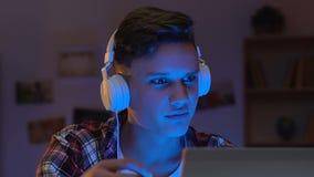 Upphetsad tonårig grabb i hållande ögonen på video för hörlurar med mikrofon på bärbara datorn hemma och att rota för lag lager videofilmer