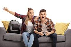 Upphetsad tonårs- pojke och flicka som sitter på en soffa och spelar en videospel arkivbilder