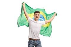 Upphetsad tonårs- pojke som rymmer en brasiliansk flagga Royaltyfri Fotografi
