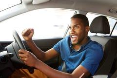 Upphetsad ung afrikansk amerikanman som kör en bil arkivbilder