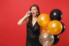 Upphetsad ung flicka i den lilla svarta klänningen som rymmer luftballonger som talar på mobiltelefonen som för angenäm konversat royaltyfria foton