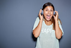 Upphetsad ung kvinna som lyssnar till musik Fotografering för Bildbyråer