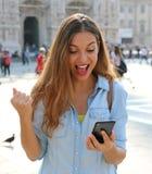 Upphetsad ung kvinna som mottar goda nyheter på linje i en smart telefon fotografering för bildbyråer