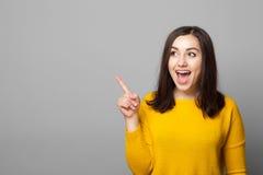 Upphetsad ung kvinna som pekar till tomt utrymme royaltyfria bilder