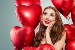 Upphetsad ung kvinna som rymmer röd hjärta för ballonger Förvånad flicka med röd kantmakeup, långt lockigt hår och gulligt leende arkivfoto