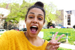 Upphetsad ung kvinna som tar selfie med fredtecknet royaltyfri foto