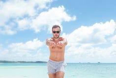 Upphetsad ung man, i att peka för baddräkt Royaltyfria Bilder