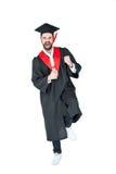 Upphetsad ung man, i diplom och att triumfera för avläggande av examenhatt hållande Royaltyfria Bilder