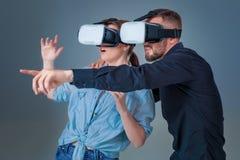 Upphetsad ung man och kvinna som har gyckel med exponeringsglas för en VR Royaltyfri Bild