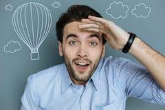 Upphetsad ung man som ler och håller ögonen på att flyga för ballonger för varm luft Arkivfoto