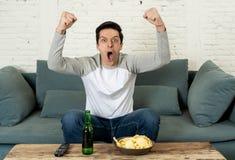 Upphetsad ung man som sitter på den hållande ögonen på fotbollen för soffa Sportsupporter- och fanbegrepp arkivfoto