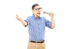 Upphetsad ung man som sjunger på mikrofonen Royaltyfria Foton