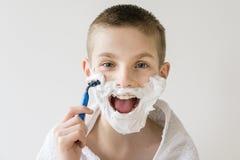 Upphetsad ung pojke som rakar framsidan med rakkniven Royaltyfria Bilder