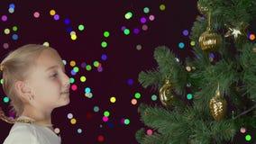 Upphetsad ung vit flicka som dekorerar julträdet och med lyckligt se till granträdet Förbereda sig för glad jul och lager videofilmer