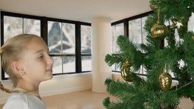Upphetsad ung vit flicka som dekorerar julträdet och med lyckligt se till granträdet Förbereda sig för glad jul stock video