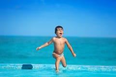 Upphetsad unge i ultrarapid av banhoppningen in i vatten Royaltyfri Bild