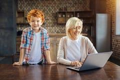 Upphetsad unge som sammanfogar hans farmor som arbetar på bärbara datorn arkivfoto