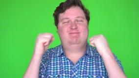 Upphetsad vinnareman som firar segra något Jätteglad ung man som gör vinnaregest på den gröna skärmen arkivfilmer