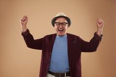 Upphetsad vuxen man som upp sätter hans nävar och att skratta arkivfoto