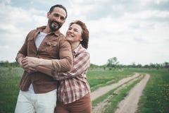 Upphetsade älska par som kopplar av på grässlätt fotografering för bildbyråer