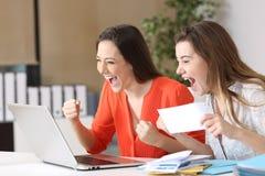 Upphetsade affärskvinnor som läser goda nyheter royaltyfri bild