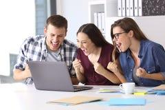 Upphetsade anställda som läser goda nyheter på kontoret royaltyfria bilder