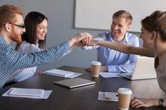 Upphetsade arbetare sammanfogar händer som är förlovade i teambuilding aktivitet fotografering för bildbyråer