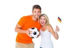 Upphetsade fotbollsfanpar som ler på kameran Royaltyfri Fotografi