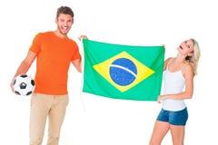 Upphetsade fotbollsfanpar som rymmer den Brasilien flaggan Arkivbilder