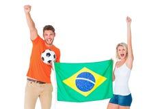 Upphetsade fotbollsfanpar som rymmer den Brasilien flaggan Arkivfoto