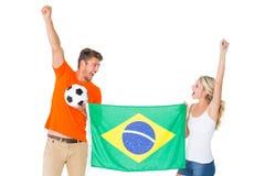 Upphetsade fotbollsfanpar som rymmer den Brasilien flaggan Royaltyfri Fotografi